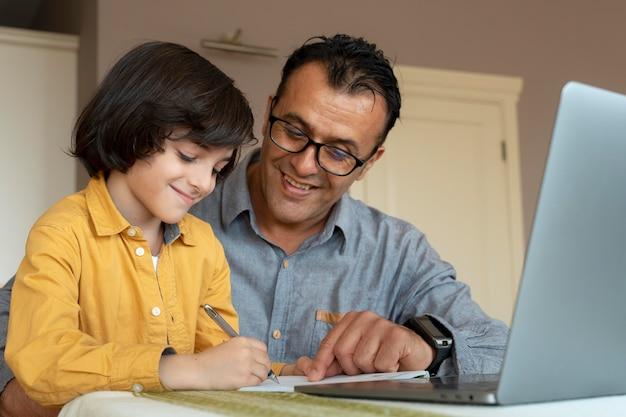 Père aidant son fils en classe en ligne