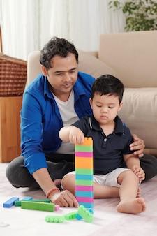 Père aidant son petit fils à construire une haute tour avec des blocs de jouets en plastique colorés
