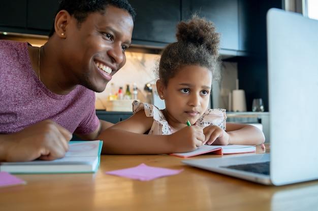 Père aidant et soutenant sa fille avec l'école en ligne tout en restant à la maison