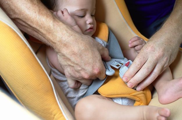 Père aide à attacher la ceinture de sécurité du siège d'auto