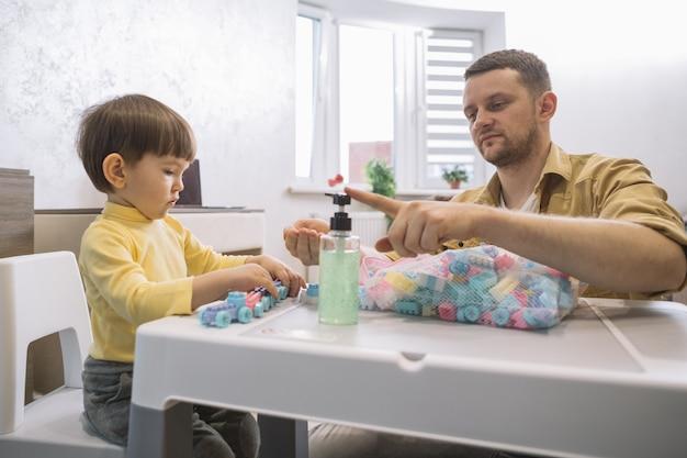 Père à l'aide de désinfectant pour les mains sur ses mains
