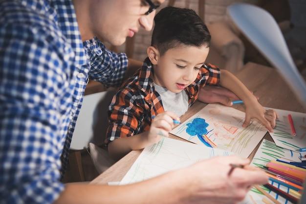 Père aide son fils à dessiner sur papier la nuit à la maison.