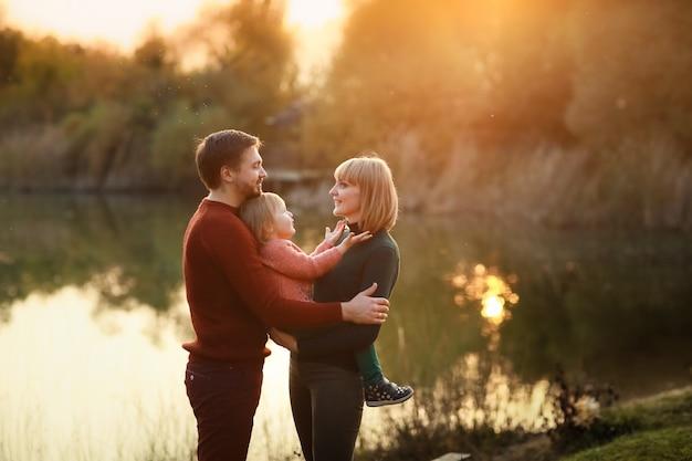 Un père aimant embrasse sa fille et sa femme à l'automne sur le fond du lac au printemps contre le coucher du soleil