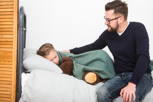 Père amenant sa fille au lit