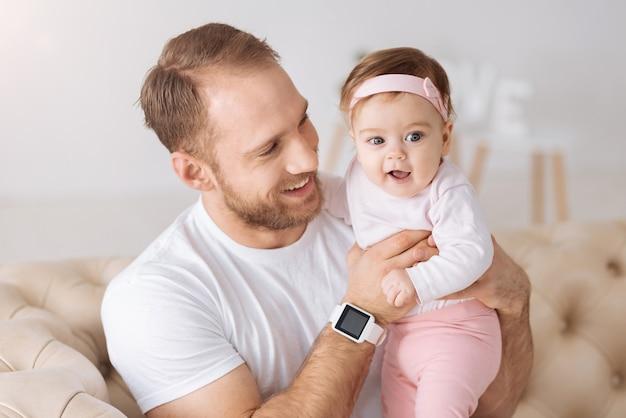 Père amour. heureux jeune père positif assis sur le canapé à la maison et étreignant son enfant tout en exprimant ses soins et son amour