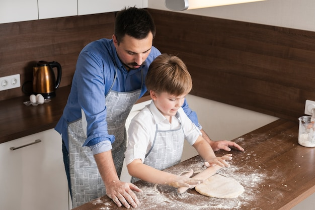 Père à angle élevé enseignant son fils à rouler la pâte