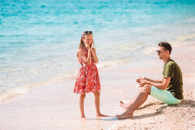 Père appliquant une crème de protection solaire à sa fille sur une plage tropicale