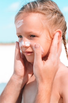 Père appliquer la crème solaire au nez de la fille.