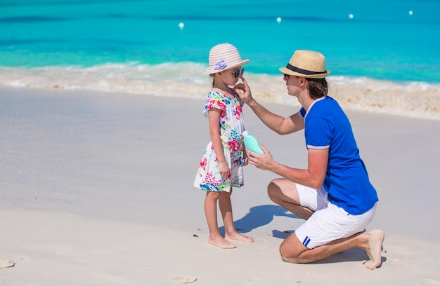 Père appliquer crème solaire sur le nez de sa petite fille