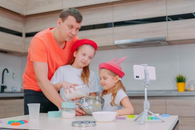 Un père apprend à deux filles à faire cuire de la pâte dans la cuisine
