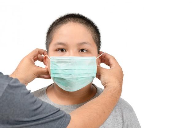 Un père apprend à son fils à porter un masque correctement et pourrait prévenir l'infection par covid 19