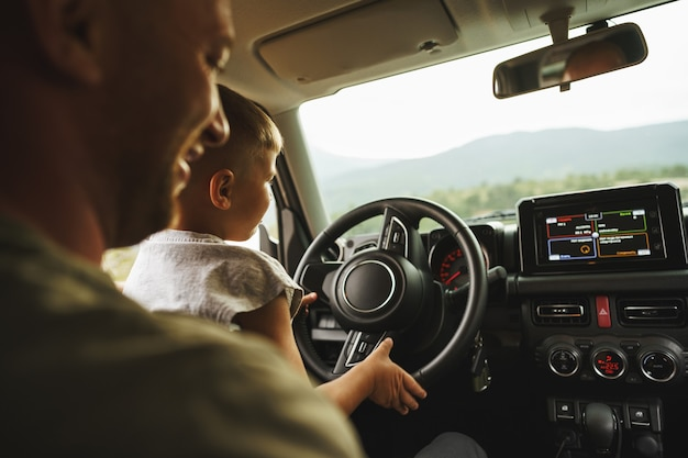 Un père apprend à son petit fils à conduire en voyage