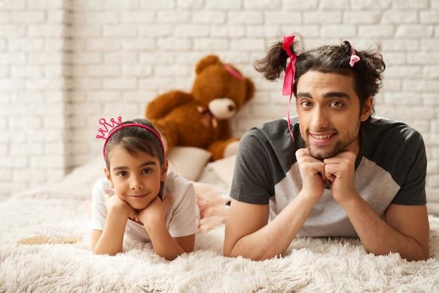 Un père arabe avec sa fille s'étendent sur un canapé.