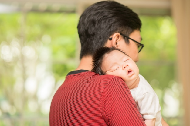 Père asain tenant son bébé sous la main
