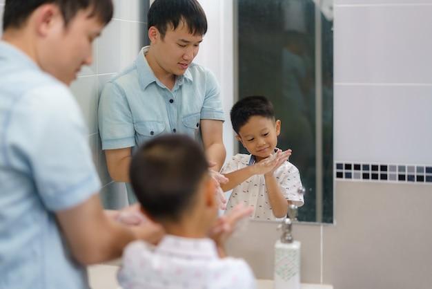 Un père asiatique apprend à son fils à se laver les mains tout seul dans la salle de bain, les pères interagissent avec leurs enfants tout au long de la journée.