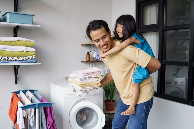 Père asiatique jouant ferroutage avec sa fille tout en faisant la lessive à l'aide d'une machine à laver