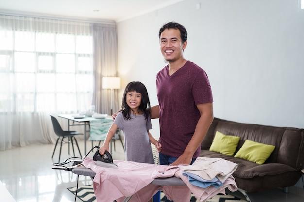 Père asiatique avec petite fille à repasser les vêtements à la maison