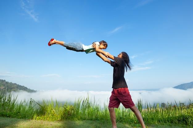 Père asiatique portant sa fille en l'air et jouant ensemble dans la belle brume et la montagne avec plaisir et amour