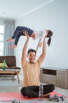 Un père asiatique utilise son enfant comme poids pour faire de l'exercice à la maison