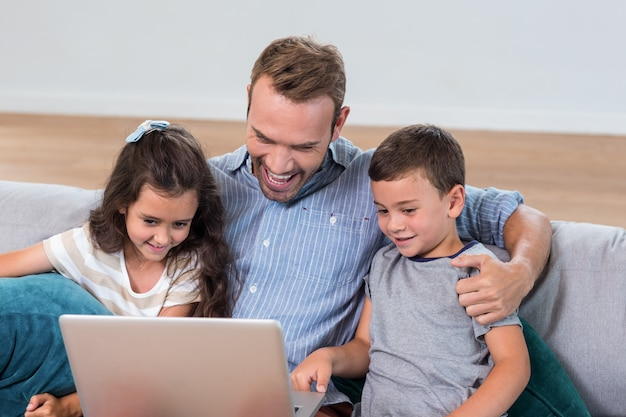 Père assis avec fils et fille et utilisant un ordinateur portable