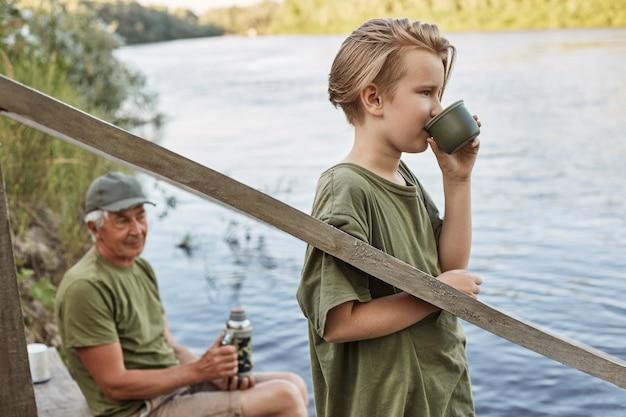 Père assis sur une place en bois menant avec un thermos dans les mains et regardant au loin à la rivière, son fils buvant du thé chaud et profitant de la belle nature.