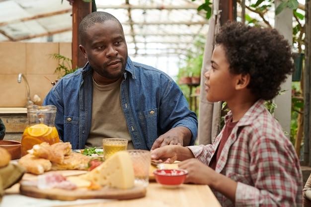 Père assis à la table à manger avec son fils parlant et dînant