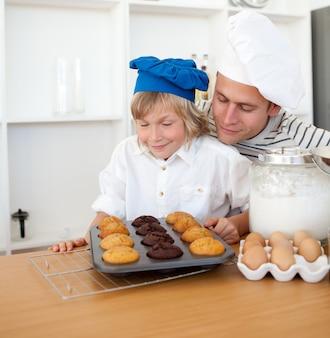 Père attentif et son fils présentant leurs muffins