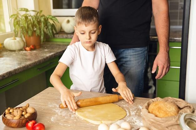 Un père attentionné apprend à son fils à cuisiner. activité intérieure. super moment en famille