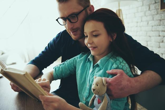 Le père aux lunettes rouges lit un livre.