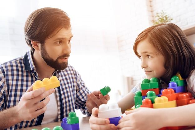 Père barbu demande à son fils de partager des blocs colorés de jouets.