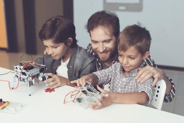 Père barbu et fils construisant un robot à la maison