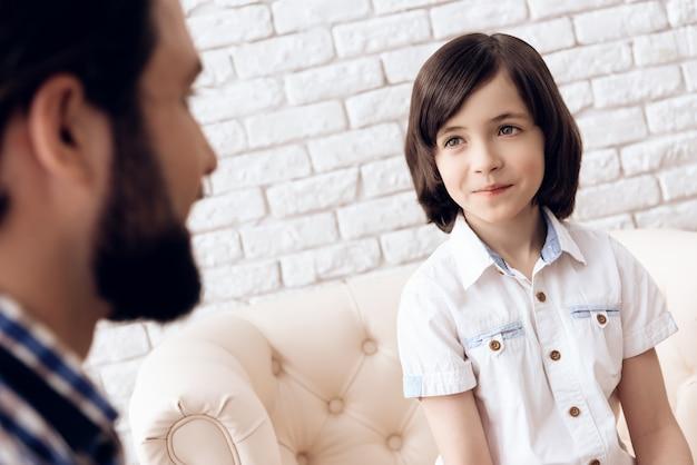 Père barbu avec son fils adolescent est assis sur un canapé en cuir.