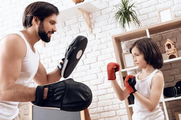 Père barbu sportif enseigne le fils à la boîte.