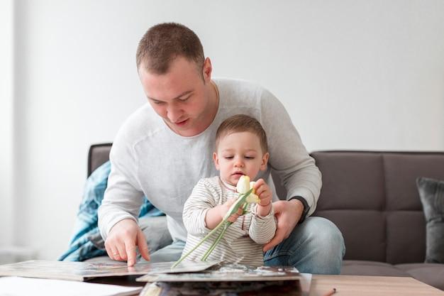 Père et bébé avec livre et fleur