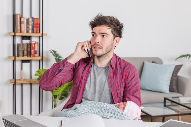 Père avec bébé parle au téléphone