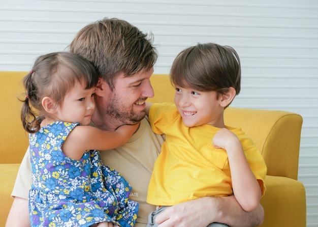 Père caucasien embrasse deux enfants, fils et fille avec amour.