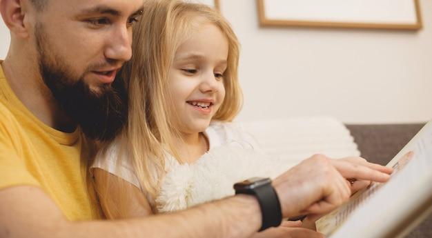 Père caucasien avec une grande barbe apprenant à sa fille à lire à l'aide d'un livre allongé sur le canapé