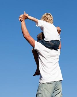 Père caucasien avec son fils sur son dos en plein air