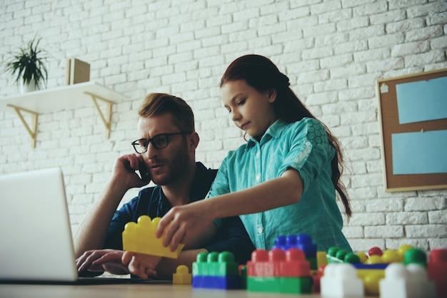 Père célibataire occupé travaille avec un ordinateur portable