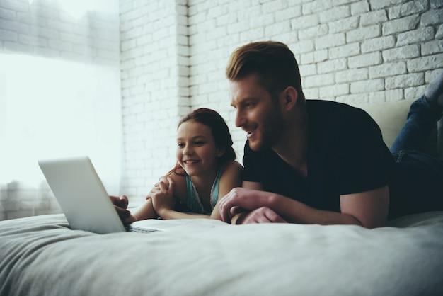 Père célibataire et sa fille se trouvent sur le lit et regardent.