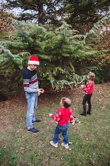 Père en chapeau de noël rouge et deux filles en chandails rouges décorant l'arbre de noël en plein air dans la cour de la maison avant les vacances
