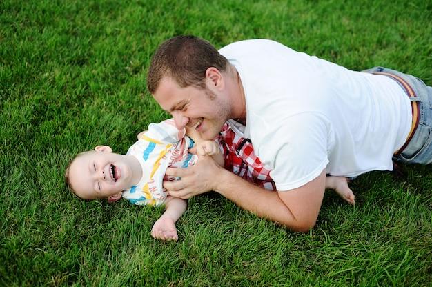 Père chatouillant jeune fils sur l'herbe