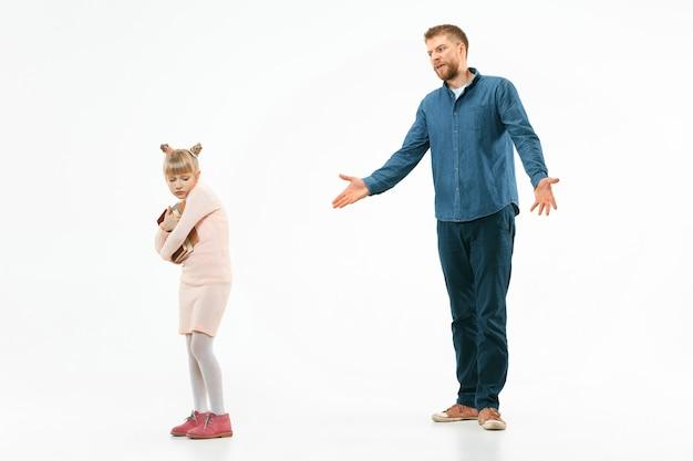 Père en colère grondant sa fille à la maison. photo de studio de famille émotionnelle. les émotions humaines, l'enfance, les problèmes, les conflits, la vie domestique, le concept de relation
