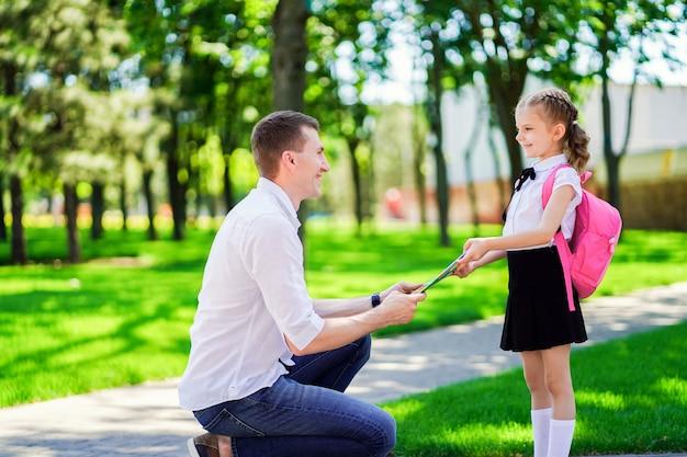 Un père conduit sa fille à l'école en première année