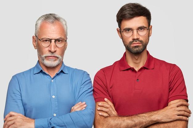 Père confiant et jeune fils adulte posant contre le mur blanc