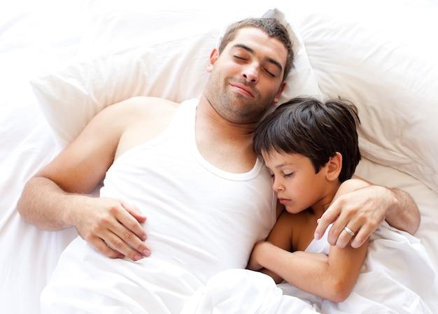 Père confiant et son fils en regardant la caméra sur le lit