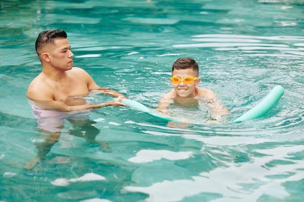 Père contrôlant son fils préadolescent dans des lunettes de natation dans la piscine avec des nouilles en mousse