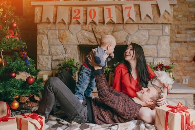 Père couché sur le plancher en jouant avec son fils pendant que sa femme regarde et cheminée fond