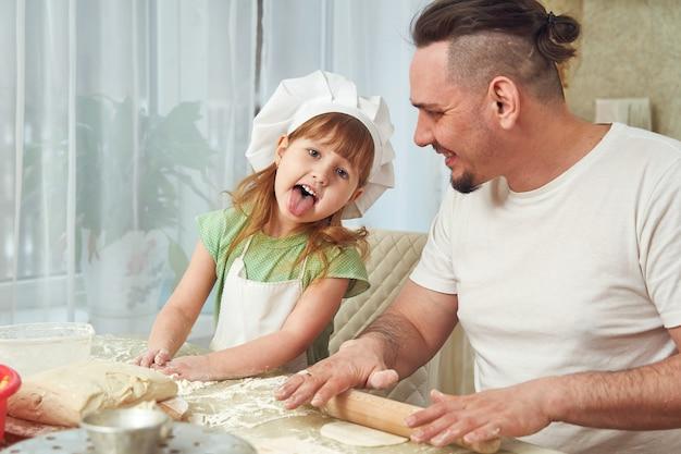 Un père cuisine avec sa fille. enfant drôle montrant la langue.