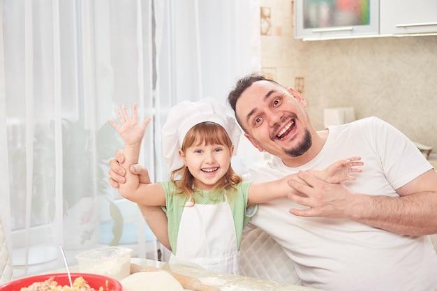 Père cuisine avec sa fille. l'homme sourit avec sa fille
